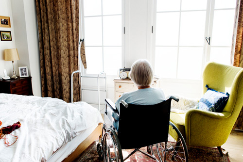 Woman in nursing home looking out window