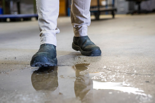 person walking on wet cement
